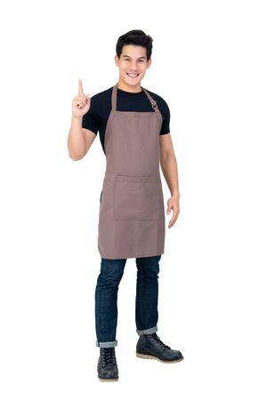 Isoliertes Porträt eines jungen attraktiven männlichen asiatischen Barista in brauner Schürze, der lächelt und die Hand nach oben zeigt