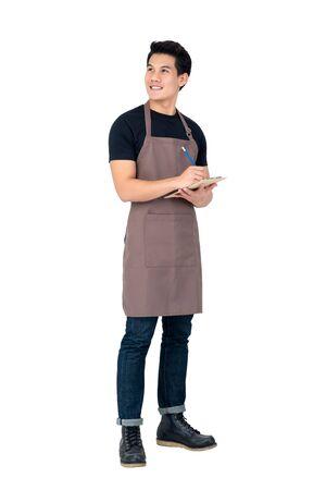 Bel homme asiatique portant un tablier comme barista debout sur fond blanc Banque d'images