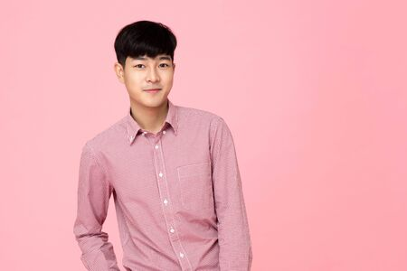 Portrait of young handsome Asian man in pink shirt, studio shot
