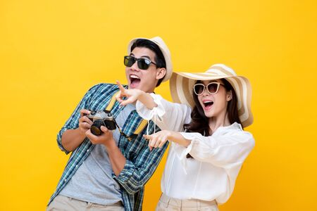 Happy excited young Asian couple tourists in colorful yellow background