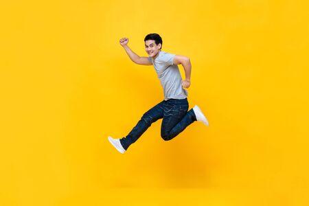 Jeune homme asiatique excité énergique dans des vêtements décontractés sautant en studio isolé sur fond jaune coloré