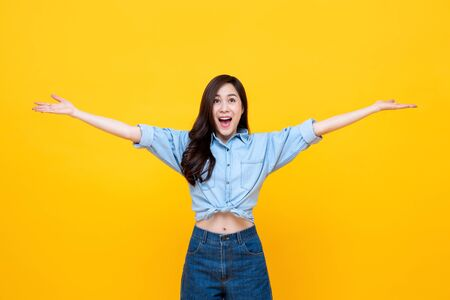 Cheerful pretty Asian woman with open hands studio shot isolated on yellow background