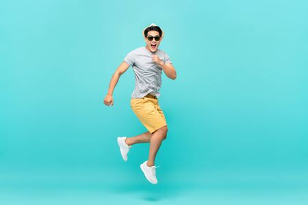 Hombre turista asiático guapo sorprendido saltando tiro del estudio aislado sobre fondo azul claro