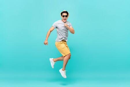 Verbaasd knappe Aziatische toeristische man springen studio-opname geïsoleerd op lichtblauwe achtergrond