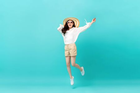 Studio shot of happy energetic asian woman wearing summer fashion attire jumping in mid-air motion isolated in light blue background Imagens