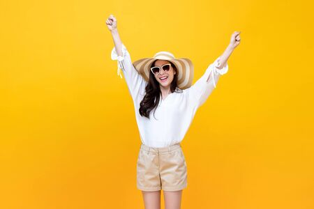 Happy smiling young Asian woman tourist raising hands up  in studio yellow isolated background