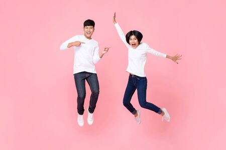 Studio shot of happy energetic asian couple wearing fashion paired attire jeans jumping in mid-air motion isolated in pink background 写真素材