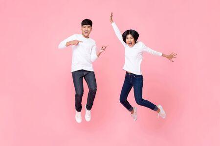 Foto de estudio de feliz enérgica pareja asiática vistiendo jeans de moda emparejados saltando en movimiento en el aire aislado en fondo rosa Foto de archivo