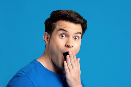 Portrait of  caucasian male model in astonished gesture with hand covering mouth in blue isolated studio background, selective focused