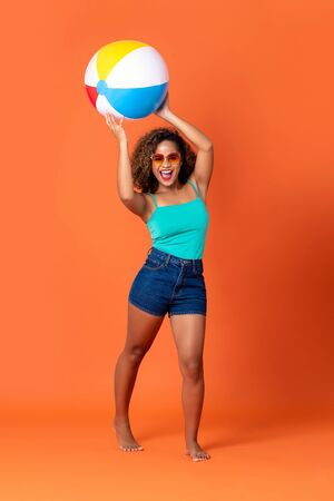 Pretty smiling African American woman in casual summer clothes with colorful beach ball on orange background