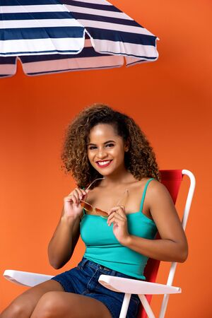 Beautiful smiling African American woman sitting on a beach chair in studio orange background Stock Photo