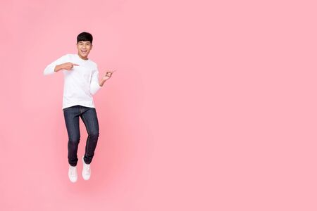 Young cheerful energetic handsome Asian man jumping with hands pointing to copy space aside studio shot isolated on pink background