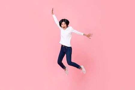 Studio shot di una donna asiatica energica felice che indossa abiti casual che salta in movimento a mezz'aria isolato in uno sfondo rosa