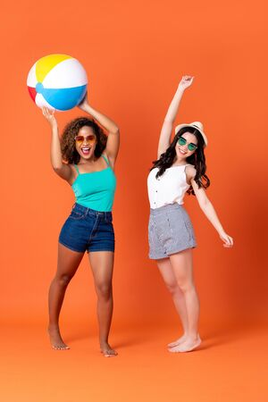 Happy African American and Asian woman friends in casual summer clothes with colorful beach ball in coral orange background Stock Photo