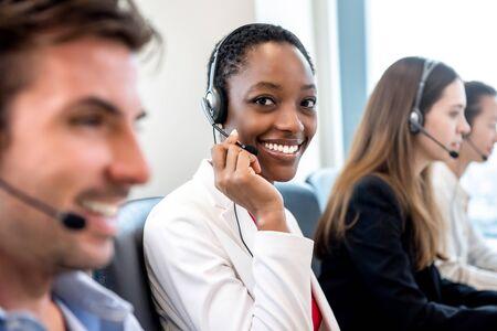 Lächelnde schöne afroamerikanische Frau, die im Callcenter-Büro mit einem vielfältigen Team als Kundenbetreuer arbeitet