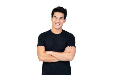 Sonriente hombre asiático guapo en camiseta negra casual con el brazo cruzado mirando a la cámara foto de estudio aislado sobre fondo blanco. Foto de archivo