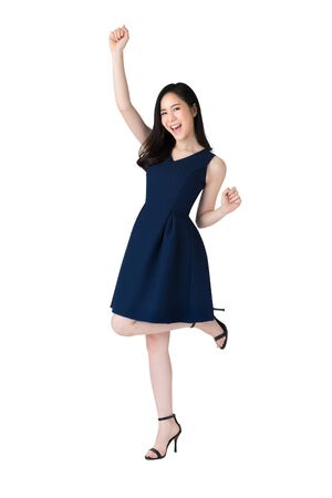 Cheerful smiling beautiful young Asian woman raising one arm and leg expressing happiness and success studio shot isolated on white background
