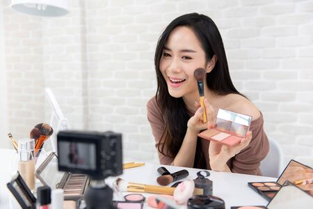 Young beautiful Asian woman beauty vlogger or blogger recording cosmetic make up tutorial video to share on social media Archivio Fotografico
