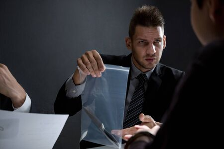 Detective showing a knife as a murder evidence in interrogation room for crime investigation and criminalistics concepts