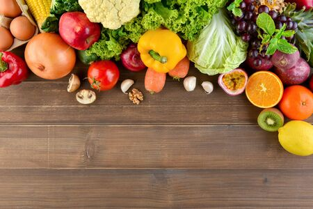 Top view of mixed  colorful healthy raw food in cladding vegetables and fruits on wood kitchen countertop background with copy space Stock Photo