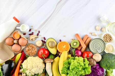 Top view of mixed  healthy food ingredients including colorful vegetables and fruits on marble kitchen countertop background