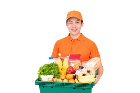 Smiling Asian delivery man in orange uniform holding grocery basket isolated on white background