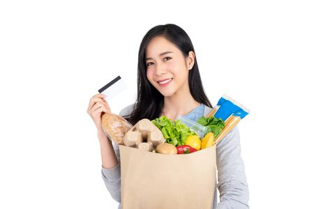 Beautiful Asian woman with credit card holding paper bag full of groceries isolated on studio white background