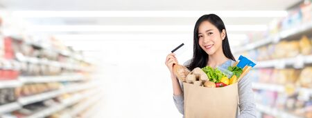 Beautiful Asian woman holding paper bag full of groceries shopping with credit card in supermarket banner background with copy space