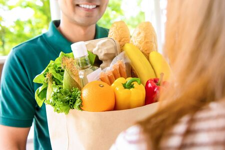 Smiling delivery man giving grocery bag to woman customer at home for online food shopping service concept Stock Photo