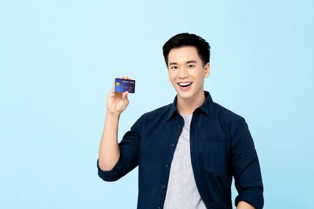 Happy handsome young Asian man showing credit card isolated on light blue background