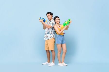 Young Asian couple in summer outfits with water guns in studio blue background for Songkran festival in Thailand and southeast Asia