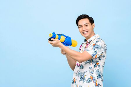 Smiling handsome Asian man playing with water gun isolated on studio blue background for Songkran festival in Thailand and southeast Asia