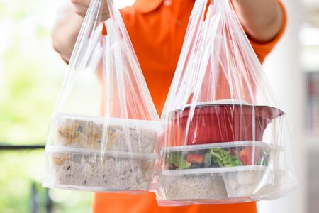 Asian food boxes in plastic bags delivered to customer at home by delivery man in orange uniform