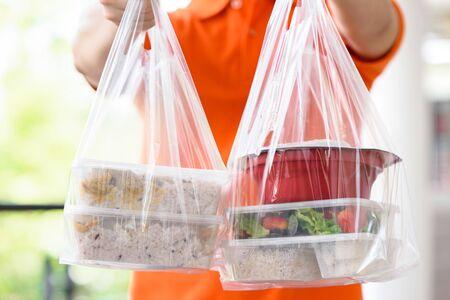 Boîtes de nourriture asiatique dans des sacs en plastique livrées au client à domicile par un livreur en uniforme orange