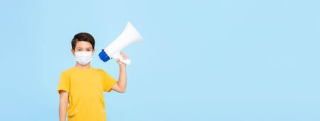 Cute young boy wearing medical mask holding megaphone isolated on light blue banner background with copy space