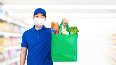 Hygienic man wearing medical mask holding grocery shopping bag in supermarket offering home delivery service Stock Photo