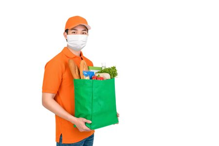 Hygienic man wearing medical mask carrying supermarket grocery shopping bag offering home delivery service isolated in white background Foto de archivo