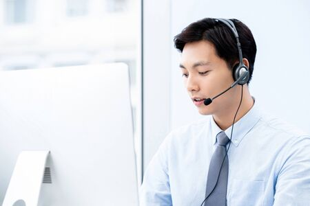 Portait of young handsome male asian call center agent looking at computer working in the office