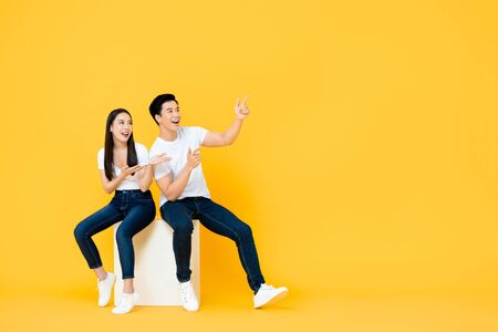 Happy surprised attractive young Asian couple pointing and looking at blank space beside in yellow isolated stuidio background