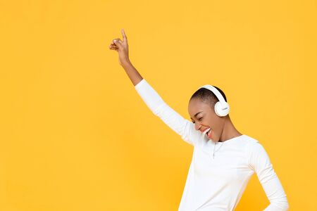 Happy young African American woman raising hand up while listening to music in wireless headphones on yellow isolated studio background