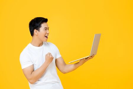 Happy young Asian man looking at laptop computer and raising his fist doing yes gesture isolated on yellow background