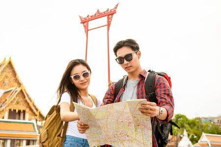 Young Asian tourist couple looking at the map while traveling in Bangkok Thailand 版權商用圖片