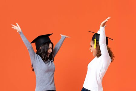 Happy excited young female students wearing graduate caps smiling with hands raising celebrating graduation day isolated on orange background