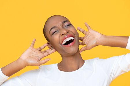African American woman laughing with joy expressing happiness and fun on yellow background 版權商用圖片