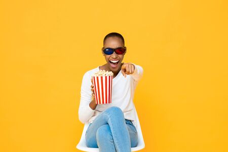 Happy African American woman with 3D glasses and popcorn laughing while watching movie on yellow studio background