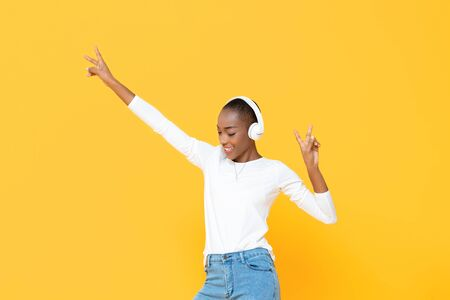 Happy African American woman listening to music on wireless headphone with hands up isolated on yellow background