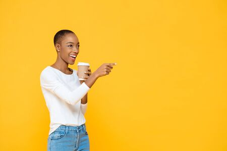 Happy beautiful African American woman drinking coffee smiling and pointing to empty space aside isolated on yellow background 版權商用圖片