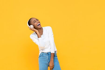 Happy African American woman laughing while listening to music on wireless headphone isolated on yellow background 版權商用圖片