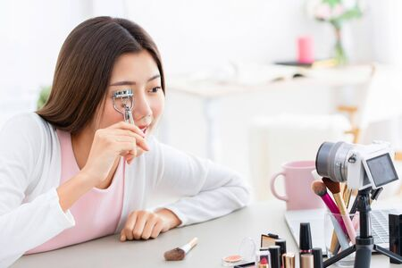 Young Asian girl beauty influencer record video while using eyelash curler at home