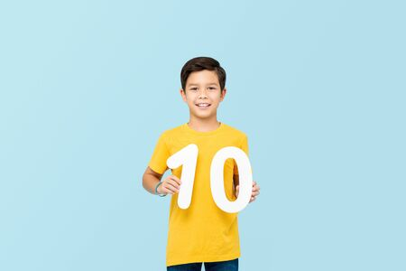 Handsome 10 year-old mixed race boy smiling and holding numbers isolated on light blue backround